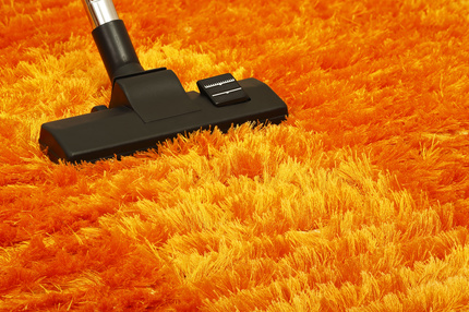 vacuum cleaner on orange fluffy carpet closeup