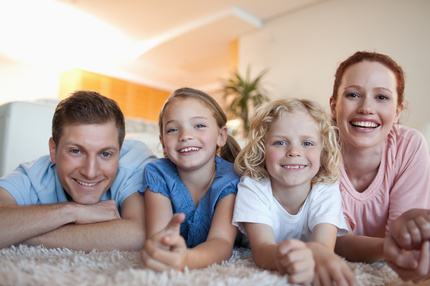 Happy smiling family on the carpet